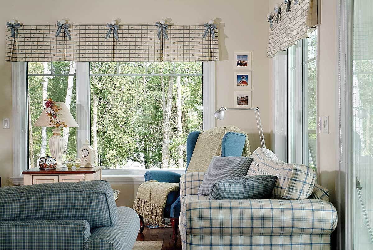 Large windows dressed in charming valances bring an abundant amount of natural light into the living room.