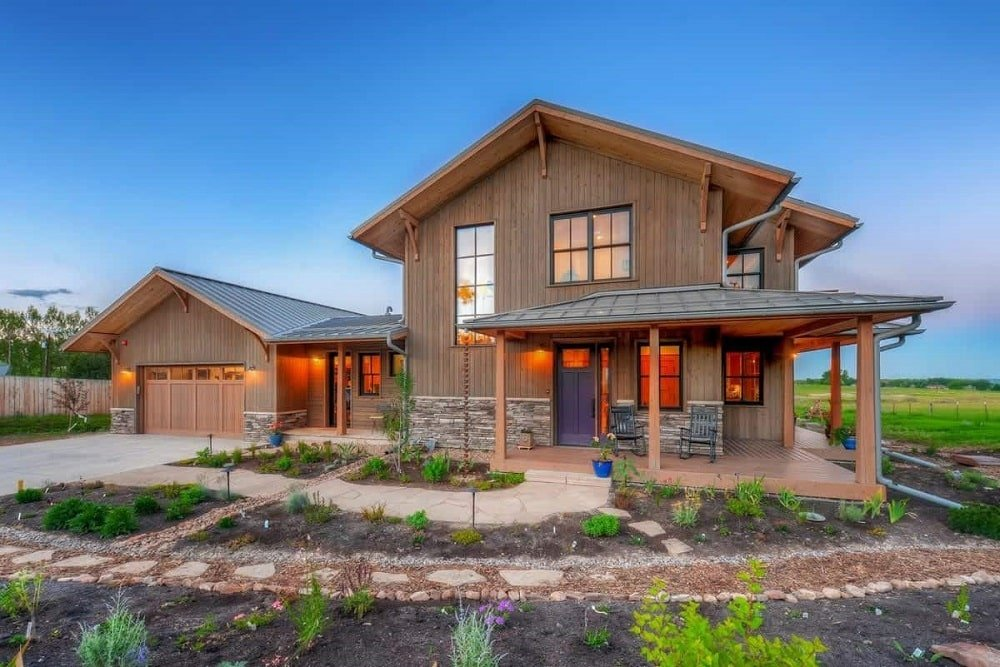 This is a look at the wooden craftsman farmhouse-style home with dark wooden exterior walls that go well with the walkway and the landscape that has various plants.