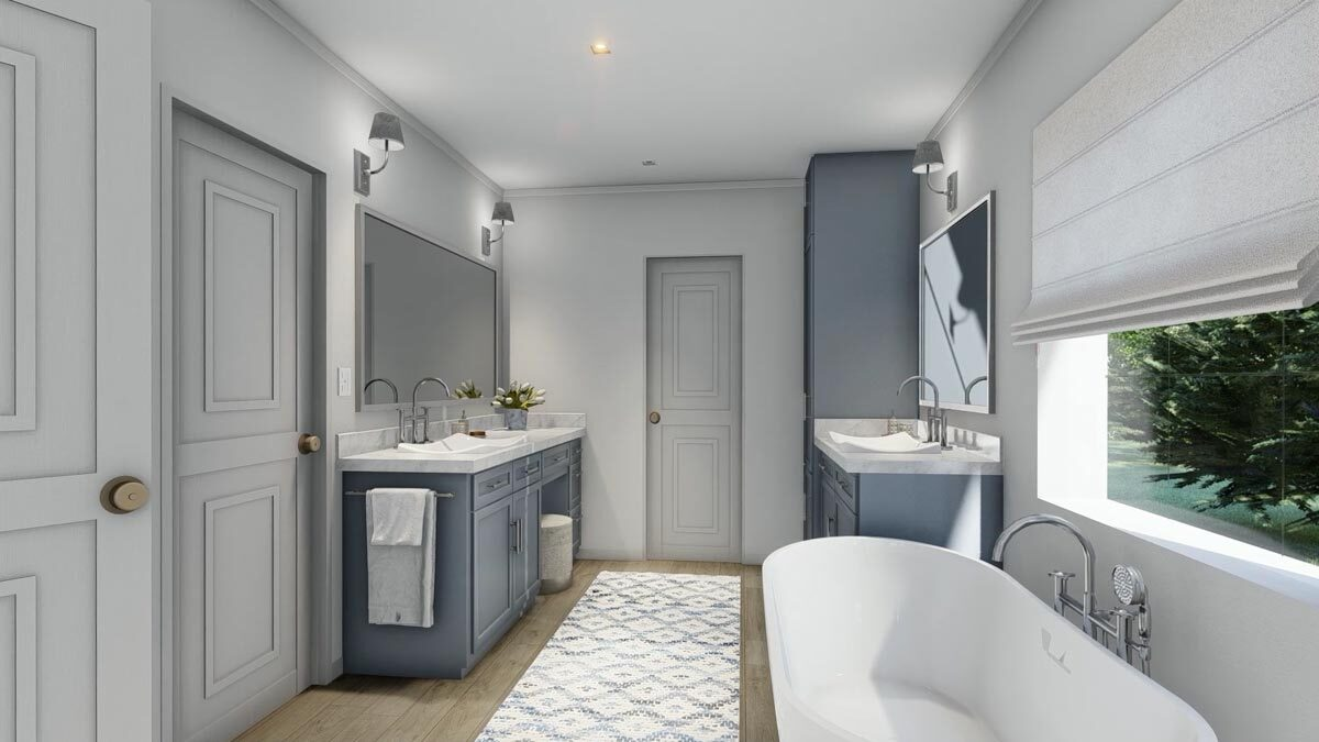 Primary bathroom with his and her vanities, a toilet room, and a freestanding tub placed under the picture window.