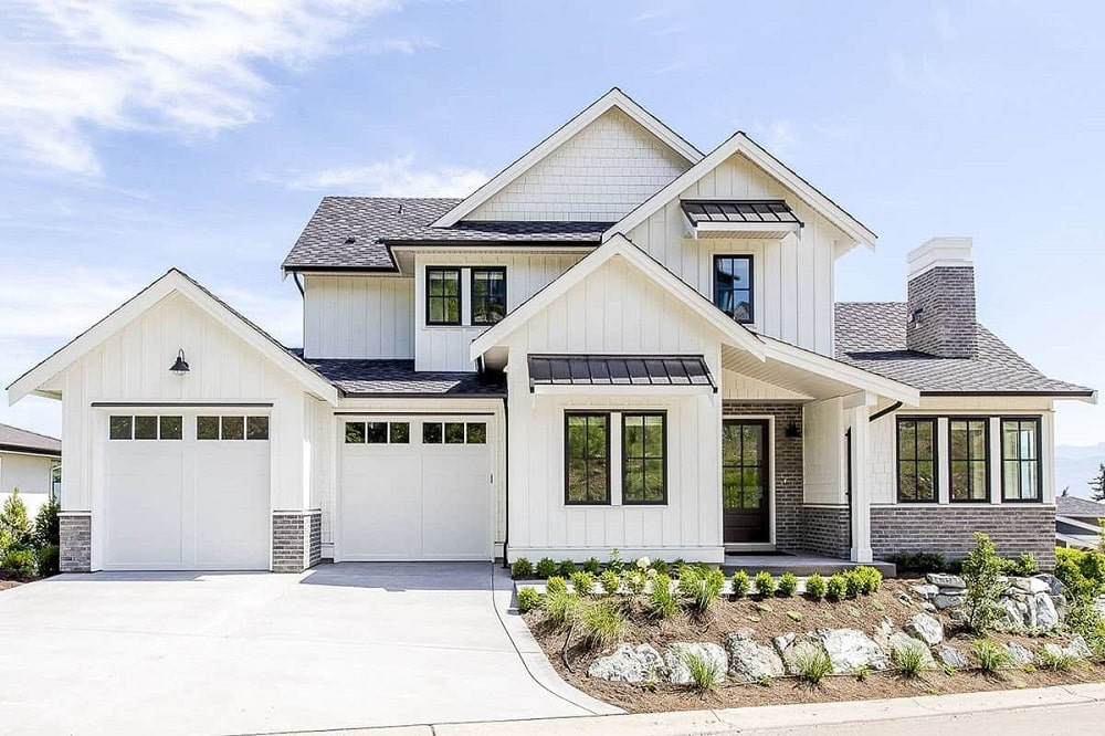 This is a front view of the farmhouse-style home with bright beige exterior walls complemented by the wide driveway, miniature front garden and multiple A-frame roofs.