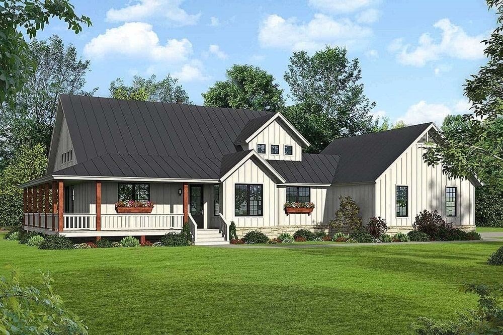 The farmhouse-style home has a dark roof to contrast the white exterior walls complemented by the wraparound porch and balcony.