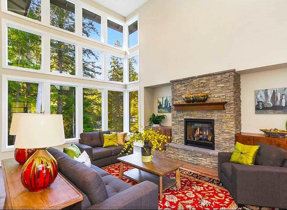The large glass wall of this living room brings in natural lighting for the beige walls that make the stone structure of the fireplace stand out along with the colorful area rug underneath the sofa set.