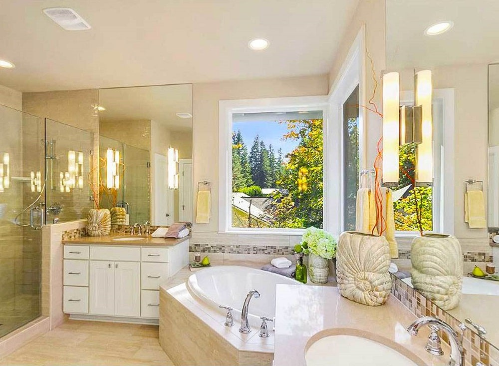 This is the primary bathroom with a large bathtub embedded onto the corner below the windows and in between two vanities with white drawers to match the white accents of the window frames.