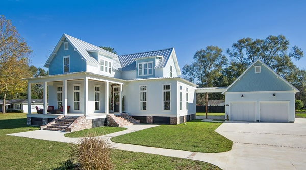 This is a front view of the house with bright exterior walls and roof to pair with the simple landscape of concrete walkways, driveways and grass lawns.