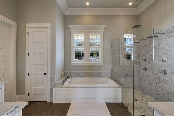 The primary bathroom has a bathtub in the middle of the glass enclosed shower area and the wooden door of the toilet area giving it an alcove with a window above.