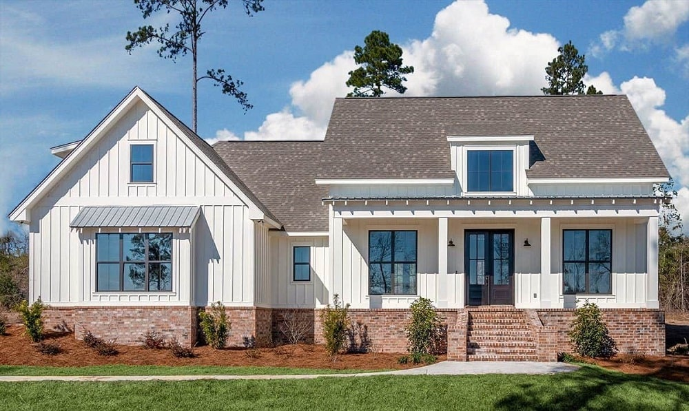 This farmhouse-style home has red bricks on its base, followed by bright beige exterior walls and topped with a gray roof that has a dormer window. These are then complemented by the landscaping.
