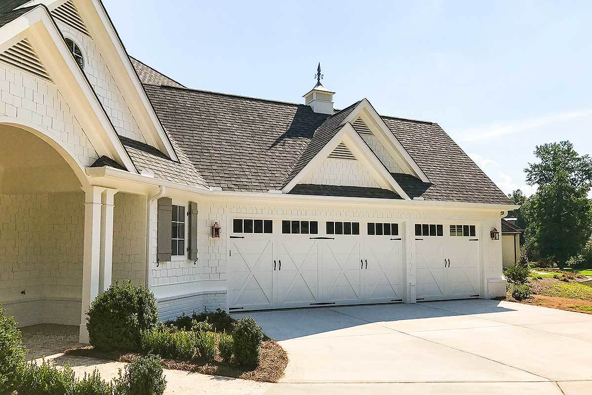 The angled garage has white oversized doors and a concrete driveway.