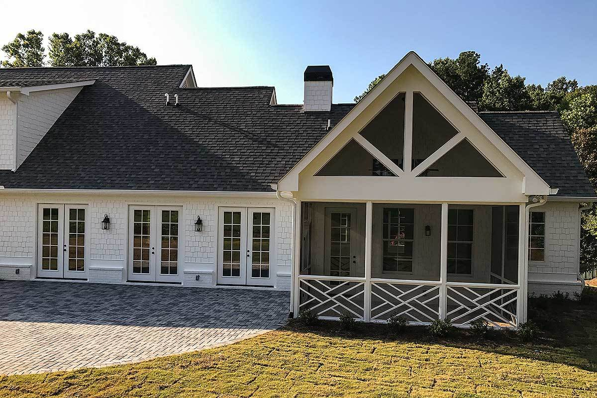 White decorative trims embellish the gabled screened porch.
