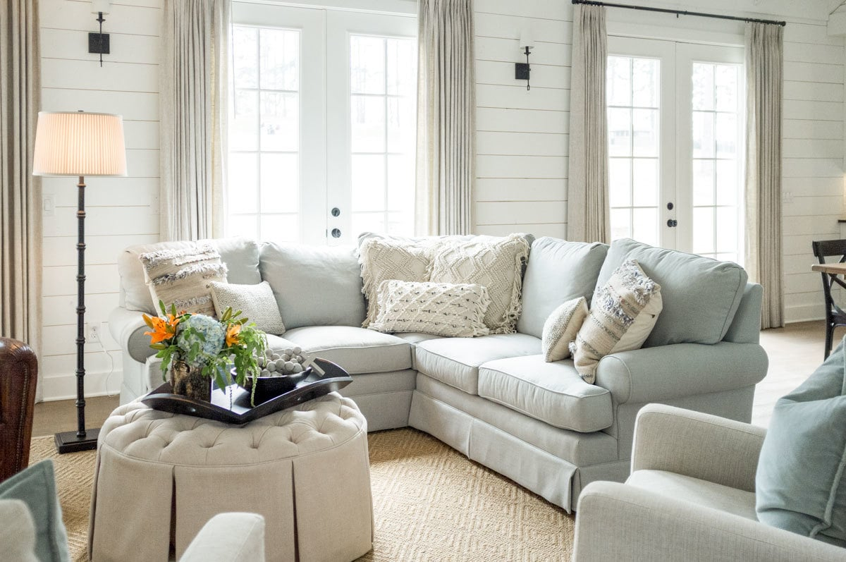 A round-tufted ottoman complements the skirted seats.