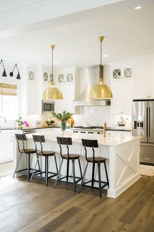 Kitchen with stainless steel appliances, a breakfast island, and white cabinetry accentuated with brass hardware.