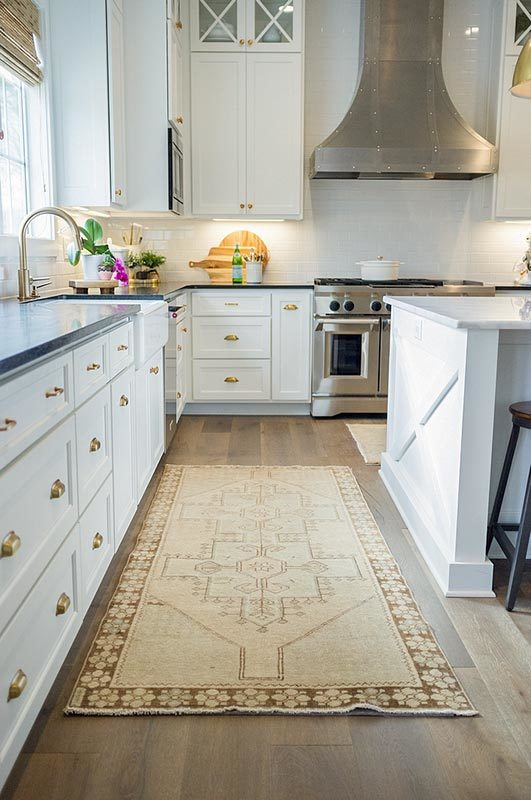 Beige rug and runner provide warmth in the white kitchen.