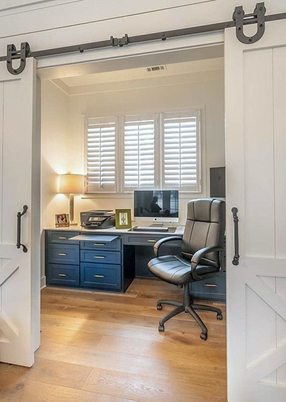 Double barn doors open to the study with a built-in desk and a leather swivel chair.