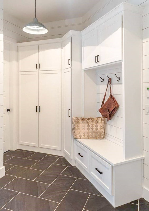 Mudroom with white cabinets, coat racks, and a storage bench.