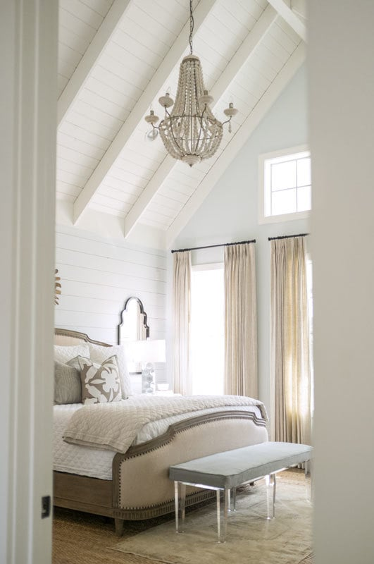 A glimpse at the primary bedroom crowned with a vaulted ceiling.