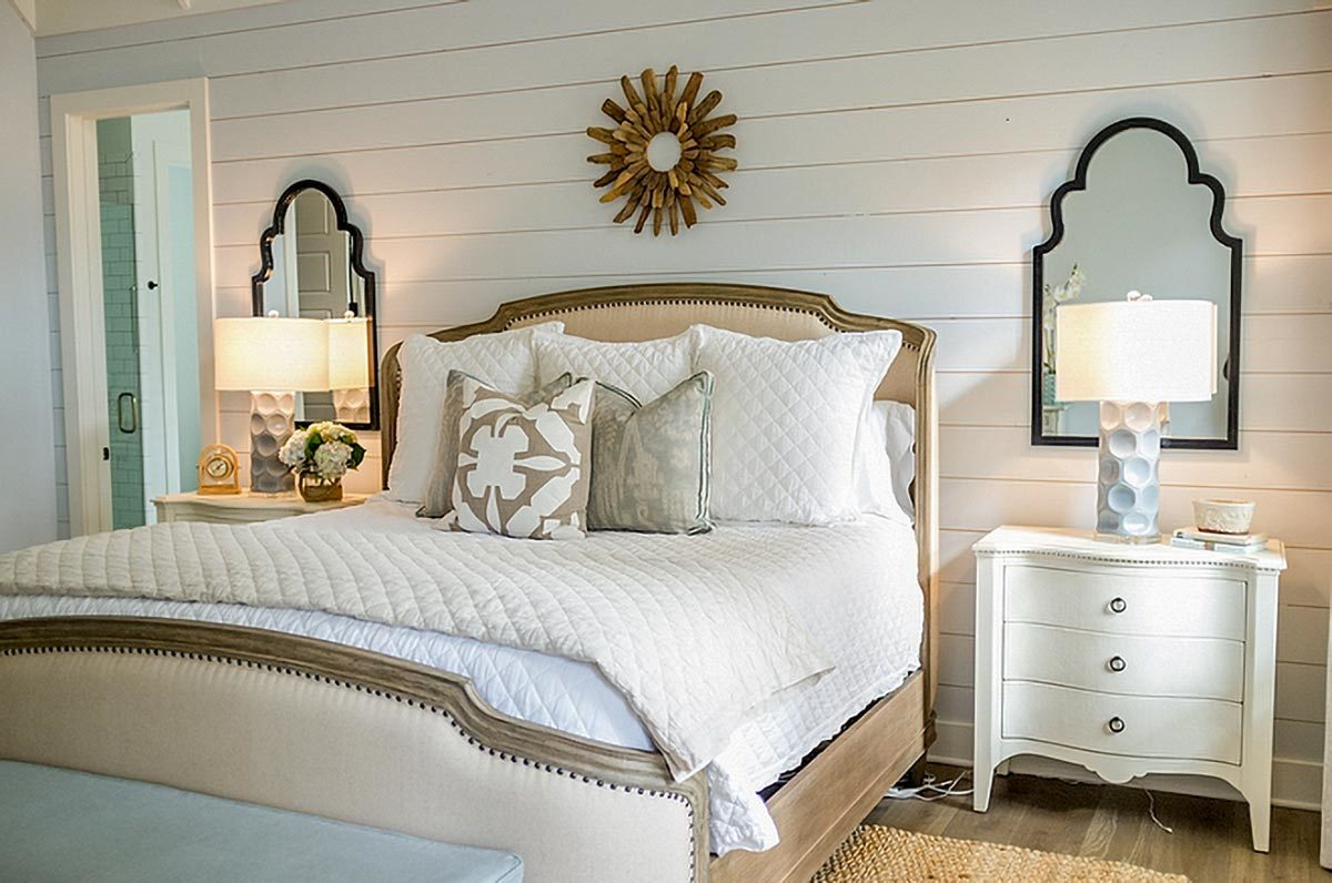 Matching nightstands along with a sunburst wall art adorn the white shiplap wall.