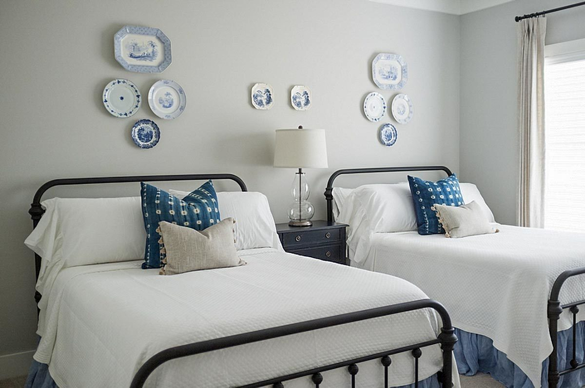 Another bedroom with two beds, a black nightstand, and gray walls mounted with decorative ceramic plates.