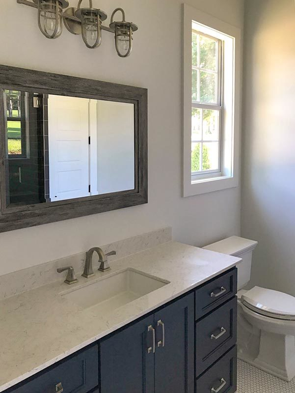 Bathroom with a toilet and a sink vanity paired with a rustic mirror.