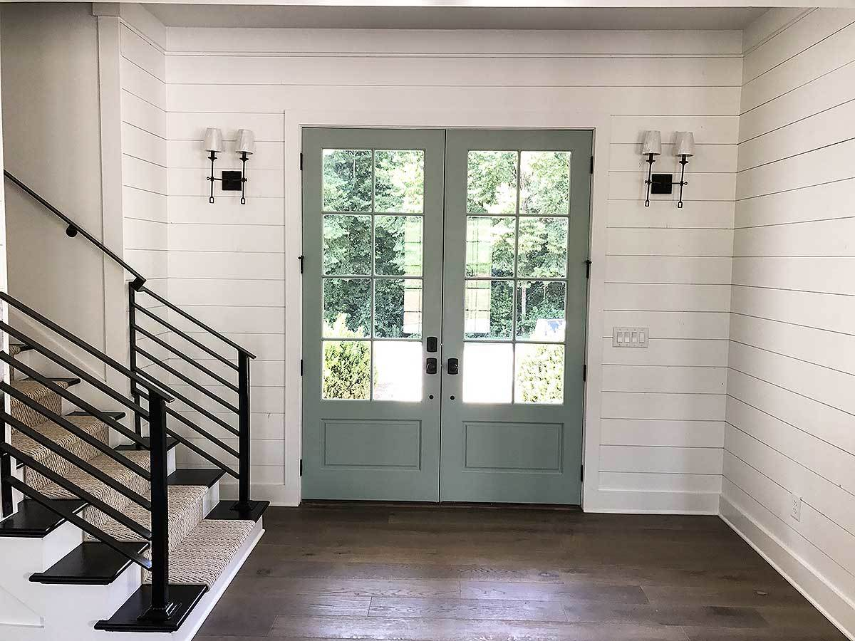 Wrought iron sconces flank the green french door.