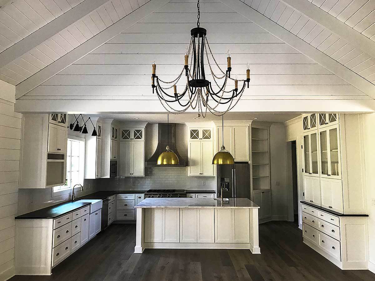 Kitchen with white cabinetry, a farmhouse sink, and a large center island.