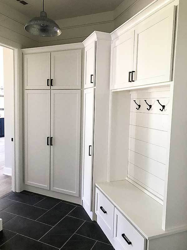 Mudroom with white cabinets and a built-in bench over herringbone tile flooring.
