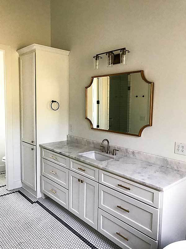 An elegant brass framed window complements the marble top sink vanity.
