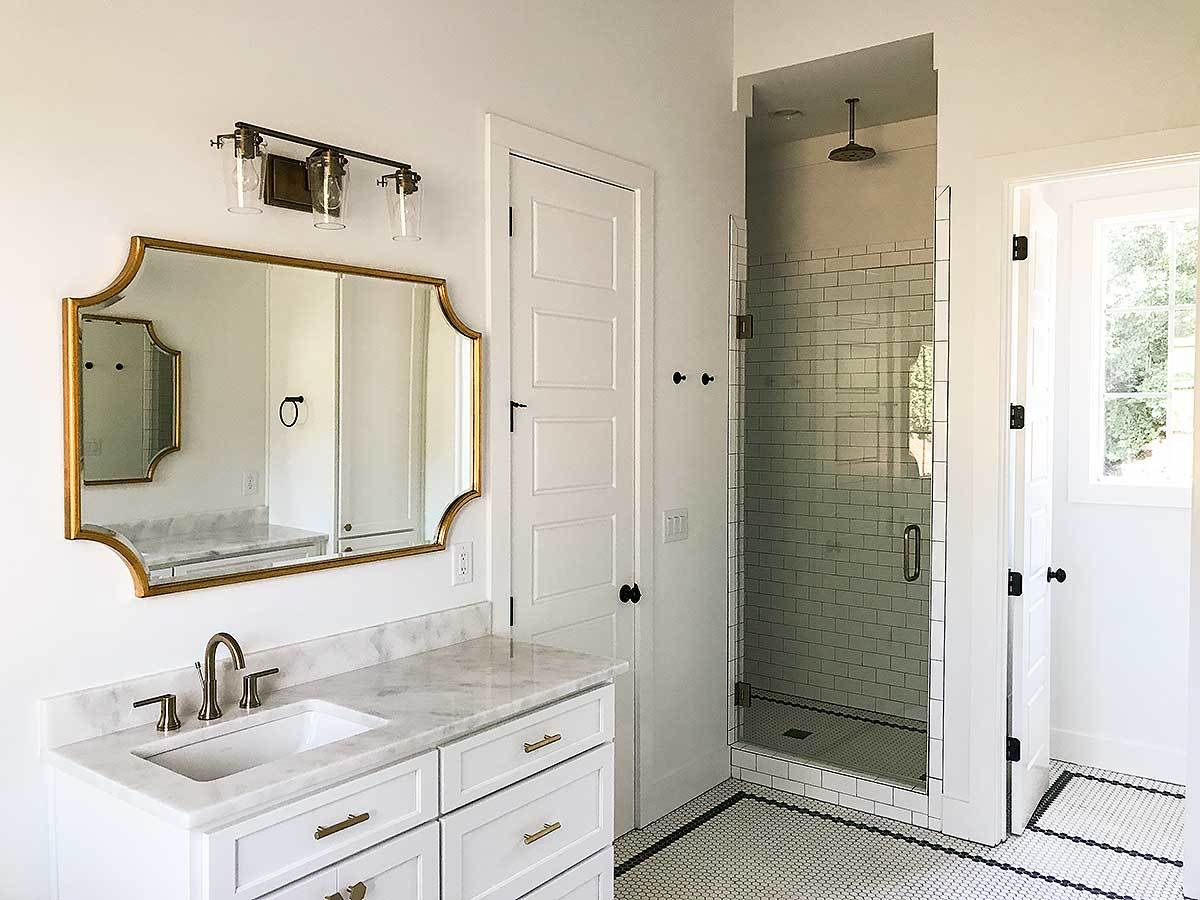 Across the vanity is a walk-in shower enclosed in a glass hinged door.