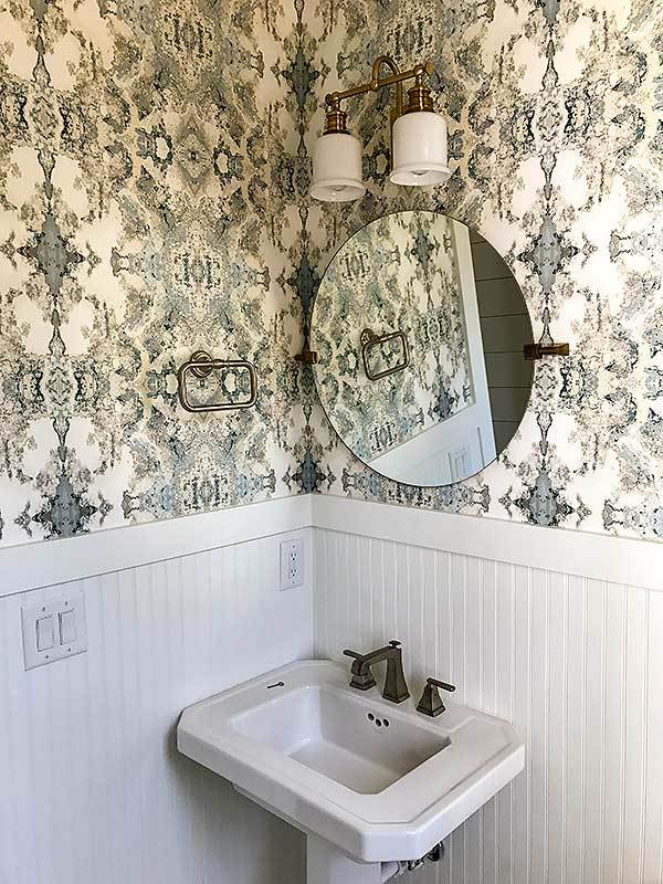 Powder room with a sink pedestal paired with a round mirror.