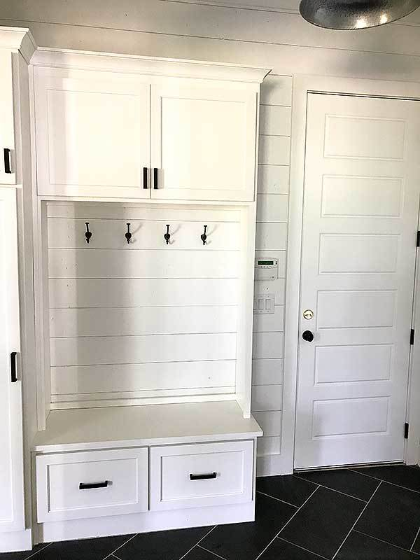 The mudroom includes convenient access to the garage via a white door.
