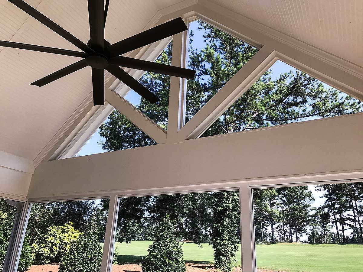 The screened porch has a vaulted ceiling, a black ceiling fan, and decorative white trims.