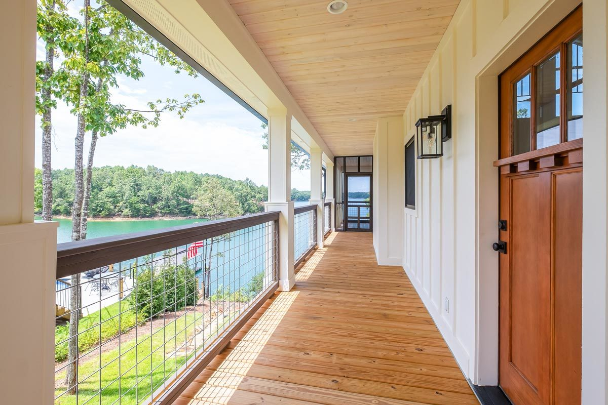 Covered porch with screen railings, wood plank flooring, and a light wood-paneled ceiling.
