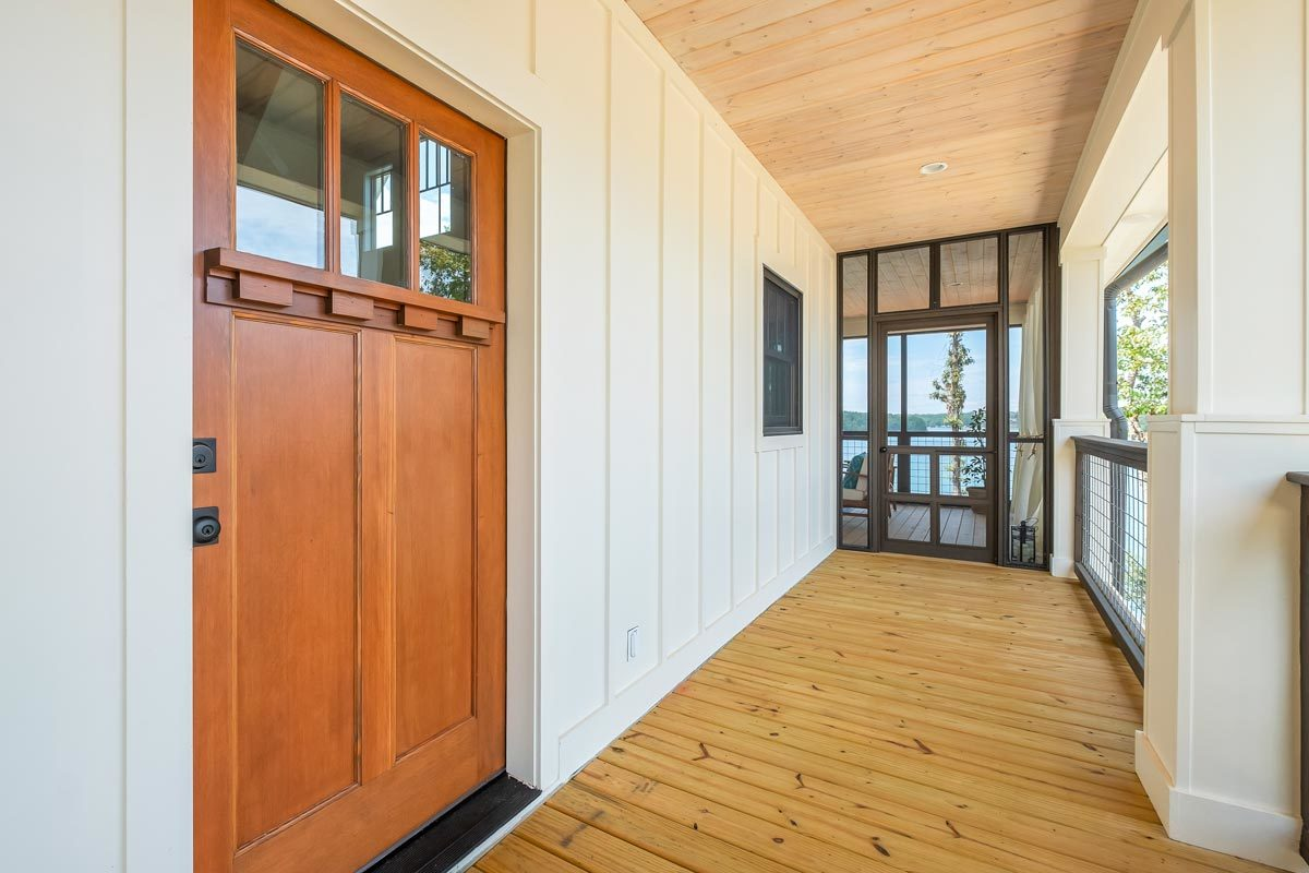 The wooden door leads to the living room while a glazed door at the far end opens to the screened porch.