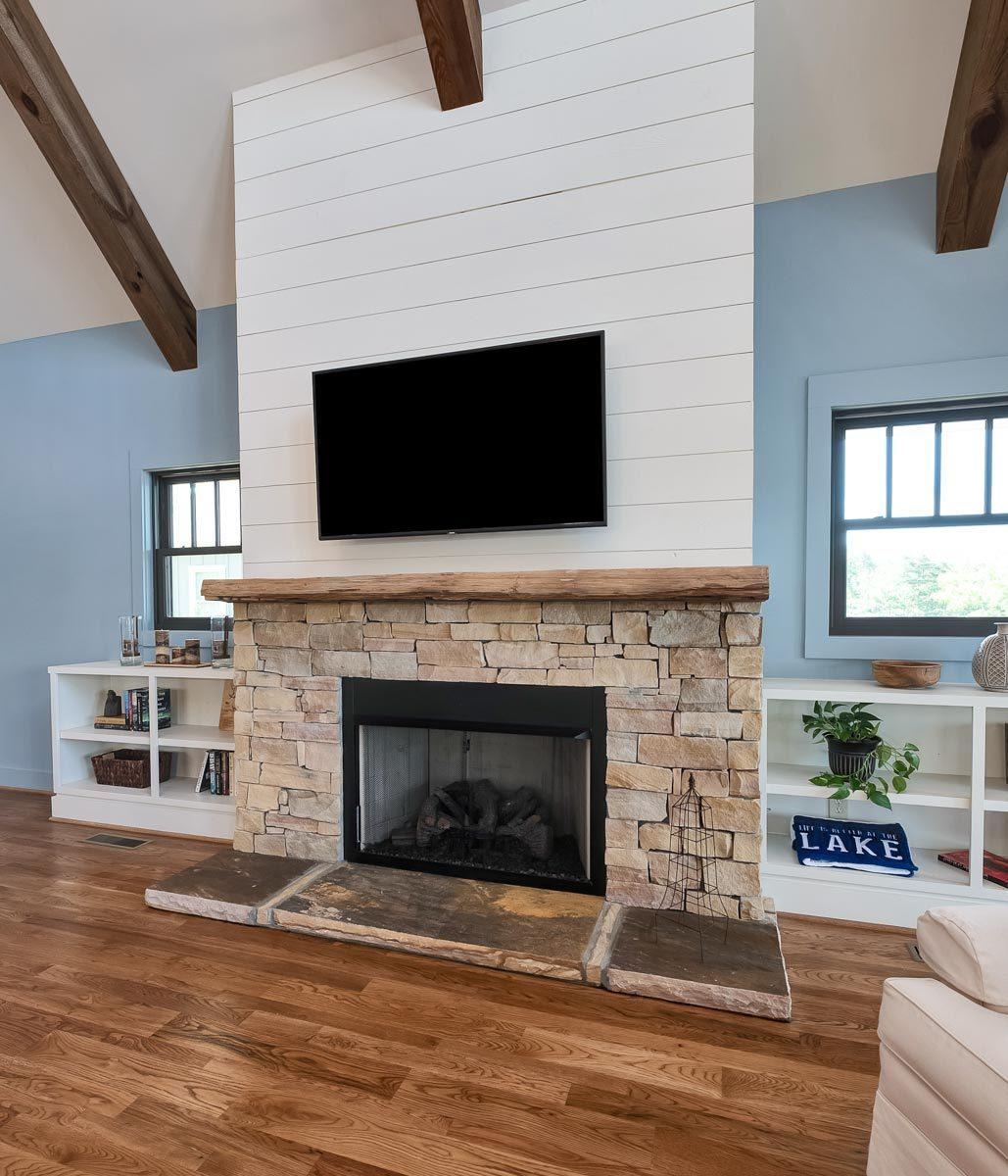 A closer look at the fireplace surrounded by white shelves and TV.