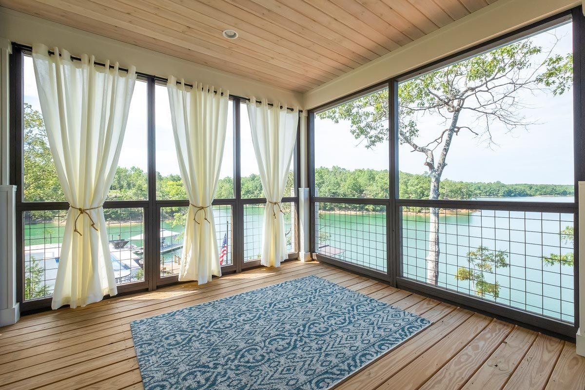 Corner windows adorned with white sheer curtains give you an amazing view of the lake.