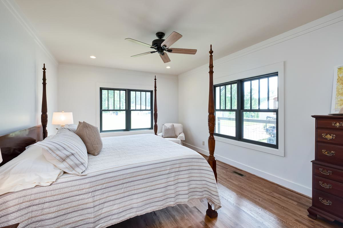 The primary bedroom includes a wooden dresser and black aluminum-framed windows that naturally brighten the space.