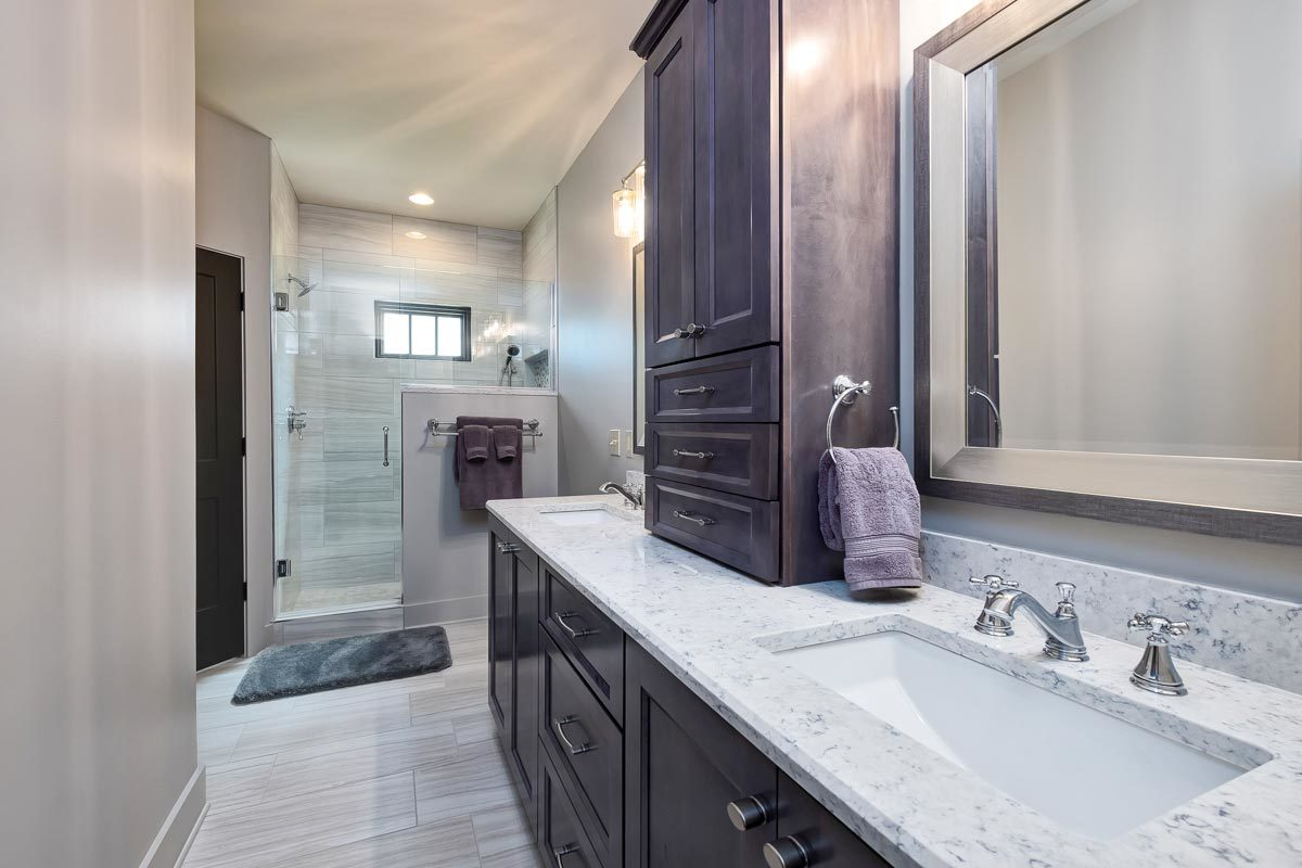 Primary bathroom with a walk-in shower and a dual-sink vanity with dark wood cabinets and granite countertop.