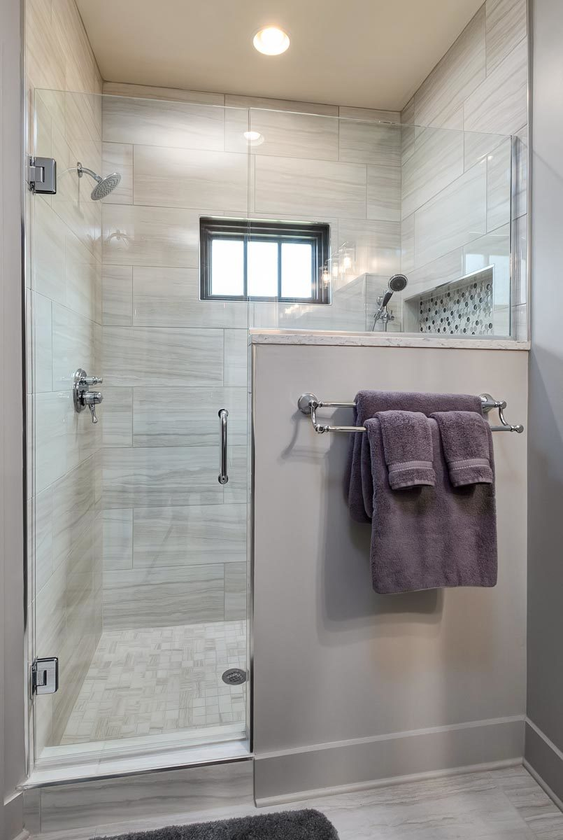 The walk-in shower has tiled walls, an inset shelf, chrome fixtures, and a glass hinged door.