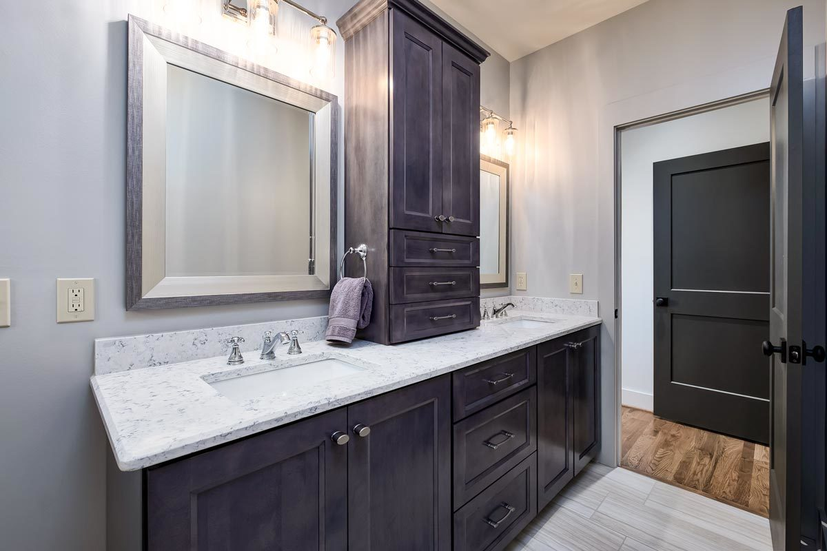 Glass sconces hanging above the framed mirrors illuminate the vanity.