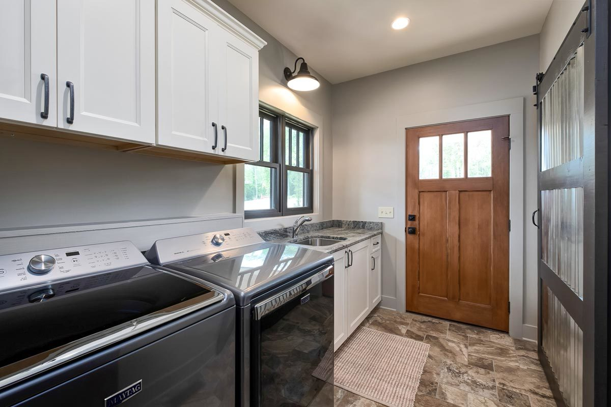 The laundry room is equipped with top-load appliances, white cabinets, and a utility sink.