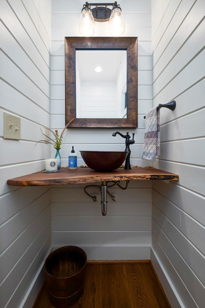 The powder room features a vessel sink on top of a wooden counter paired with a rustic mirror.