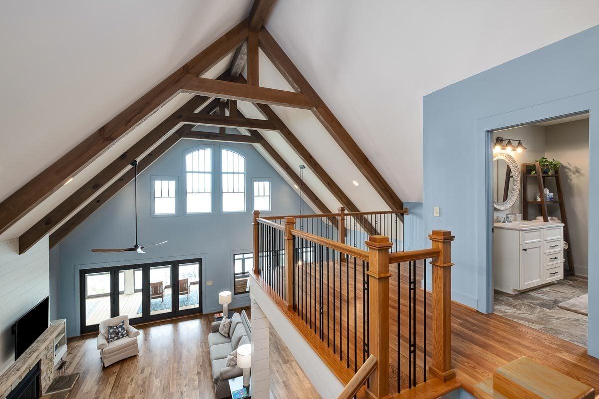 Balcony loft with wrought iron railings and hardwood flooring.