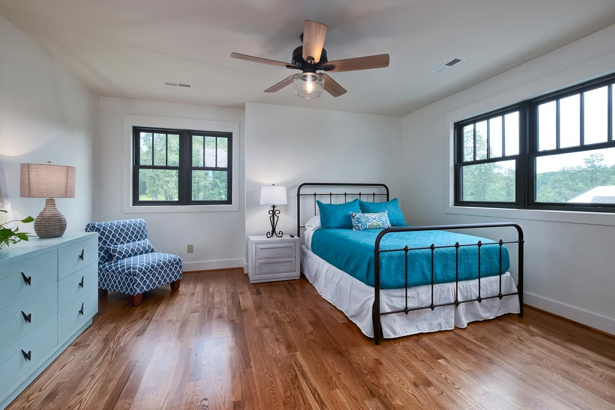 This bedroom has an iron bed, a blue dresser, and a patterned lounge chair.