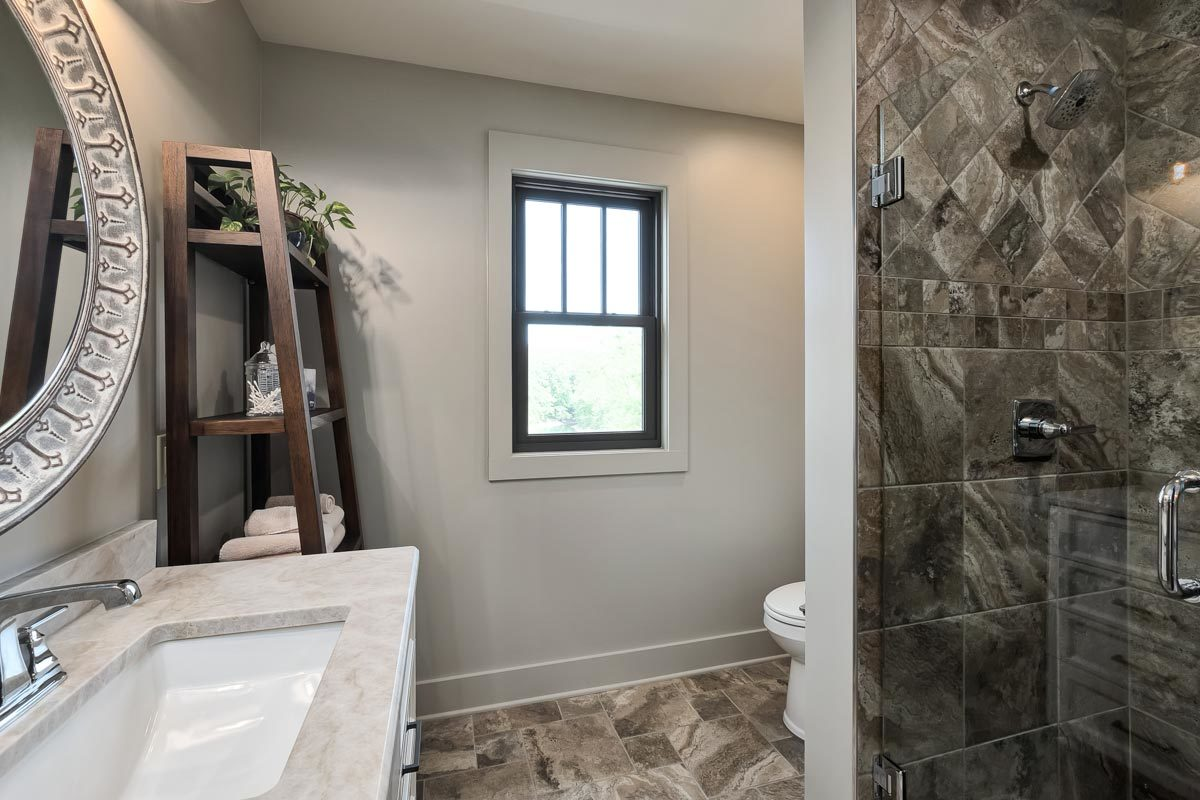 This bathroom includes a walk-in shower, a toilet, and a wooden shelving unit.
