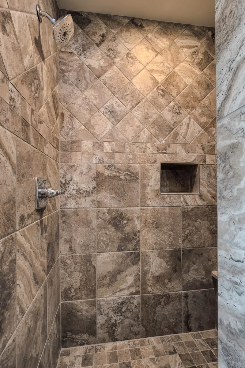 The walk-in shower has marble tiled walls, an inset shelf, and chrome fixtures.