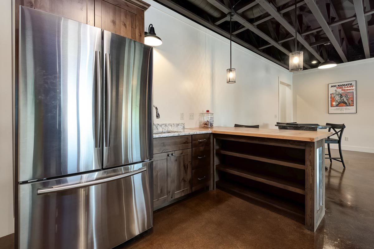 There's a kitchenette equipped with a two-door fridge, L-shaped counters, and a sink.