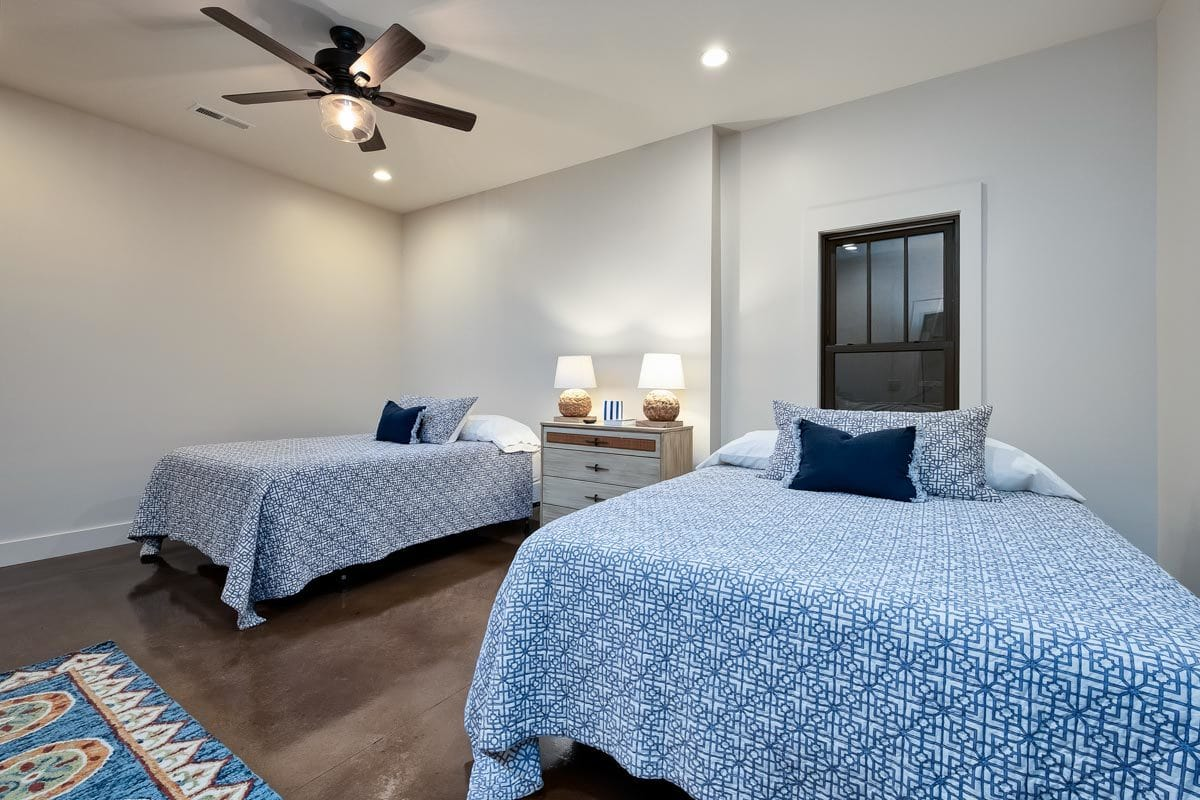 This bedroom offers two beds, a center nightstand, and a ceiling fan.