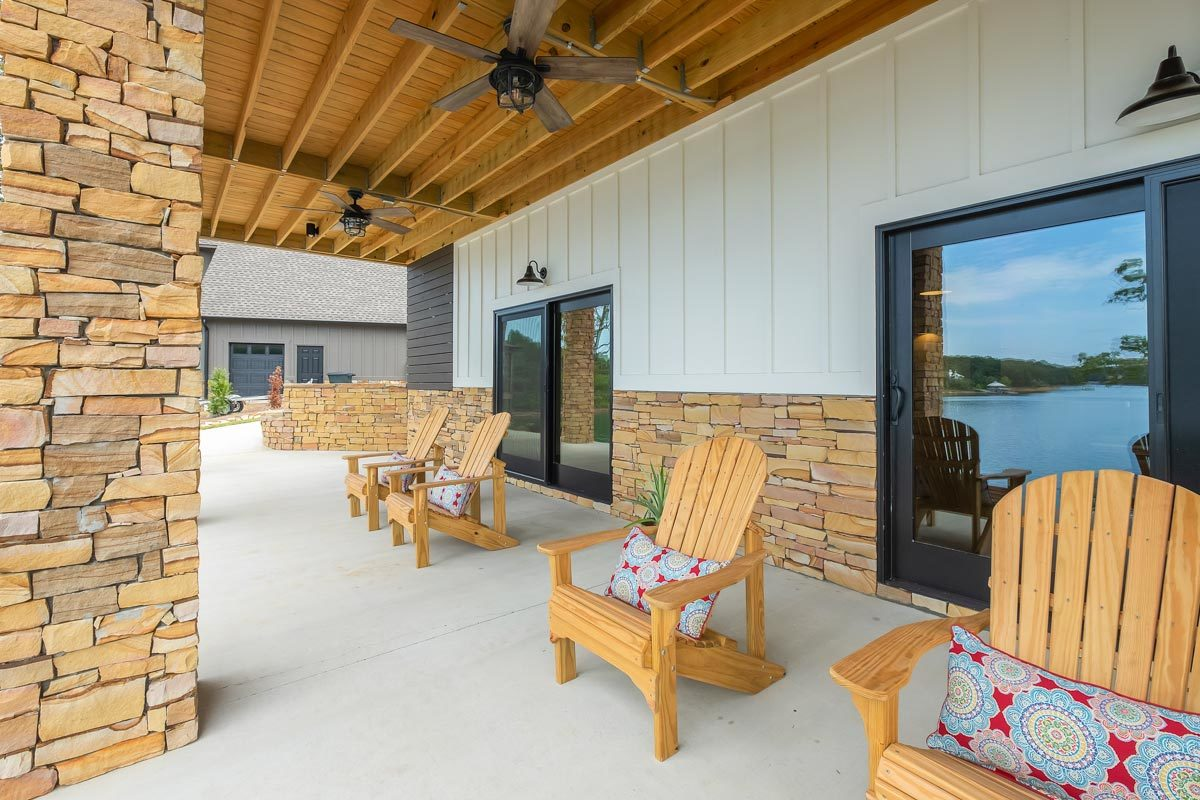 The covered patio is filled with teak lounge chairs accentuated by patterned pillows.