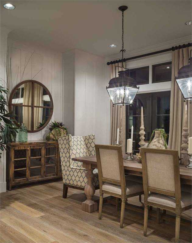 This is a close look at the dining room with a lantern pendant light over the large wooden rectangular dining table that matches the chairs and the cabinet on the far side under the mirror.