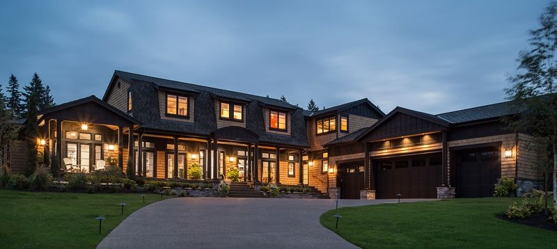 This is a nighttime view of the house exterior showcasing the warm glow of the windows and the landscaping that has a wide concrete driveway flanked by grass lawns.