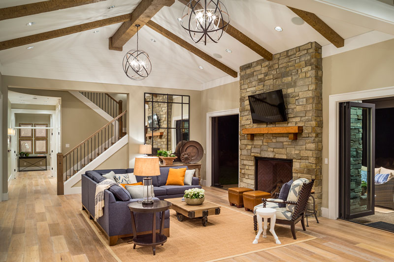 The living room has an L-shaped sectional, cozy chairs, and a wooden coffee table facing the brick fireplace and wall-mounted TV. These are then topped with a tall cathedral ceiling with exposed beams and a couple of pendant lights.