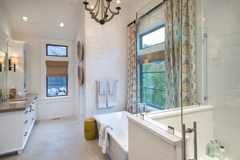 This is a close look at the primary bathroom with a glass-enclosed shower area beside the bathtub under the window and topped with a chandelier.